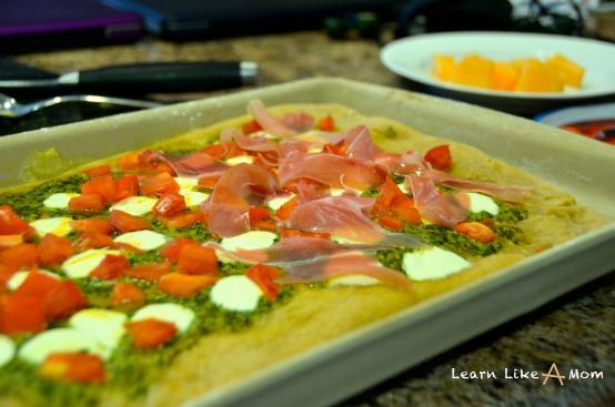 Pesto Pizza with Mozzarella, Tomatoes, and Prosciutto